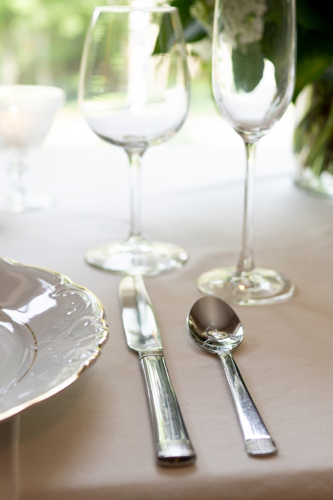 Closeup of light colored table setting featuring stemmed glassware and gleaming silver with greenery in the background