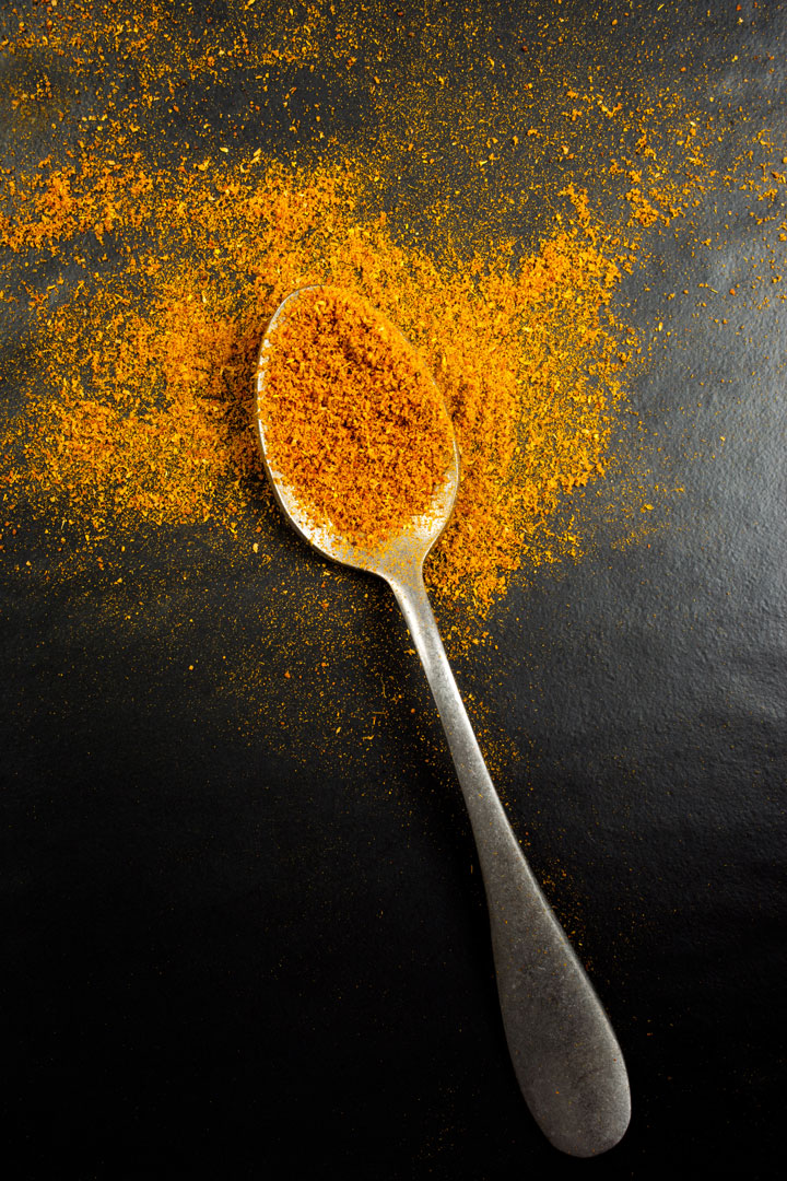 A spoonful of curry powder - an ingredient in curried veggie patties