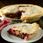 Slice of gluten-free vegan cherry apple pie with full pie in background