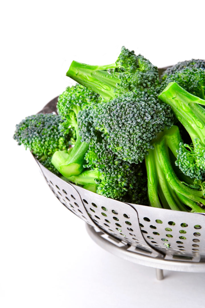 steamed broccoli with lemon in a metal steamer basket
