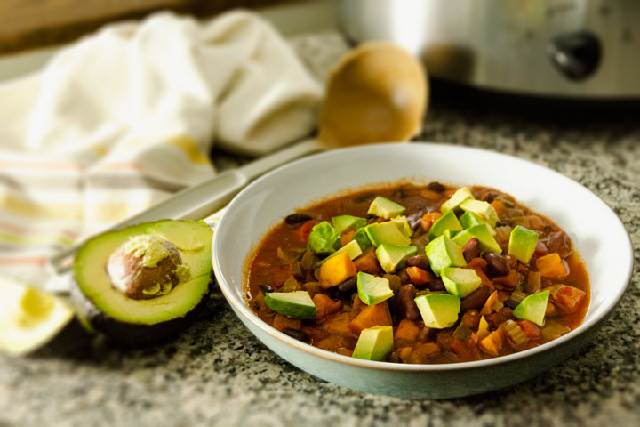 Bowl of slow cooker 3-Bean Chili with ladle and sliced avocado